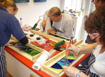Leaded stained glass garden panels being soldered on a Vitreus Art class